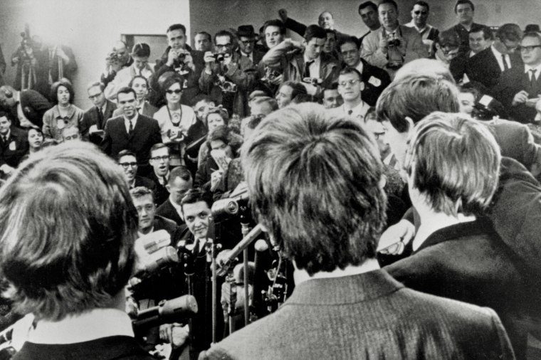 The Beatles face the media, including NBC New York's Gabe Pressman, center left, just above the microphones, upon their arrival at JFK airport in New York City on Feb. 7, 1964.