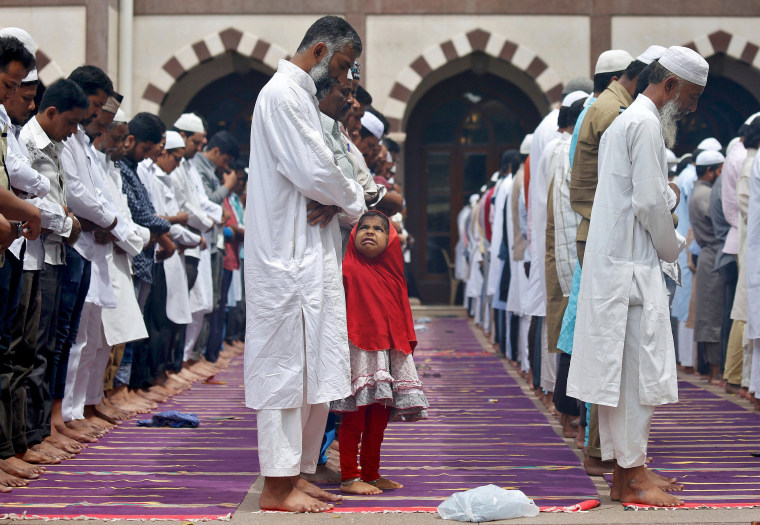 Image: A young Muslim girl reacts during Ramadan prayers