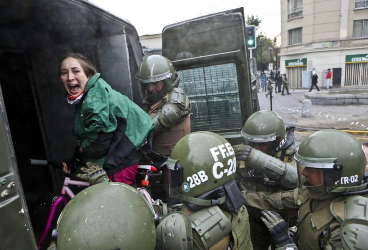 Image: A woman is arrested during a protest in Chile