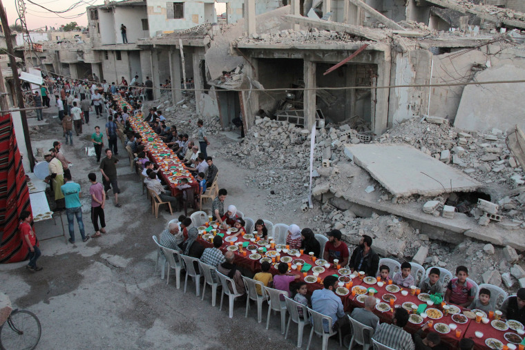 Image: Syrians share a meal on a war-torn street