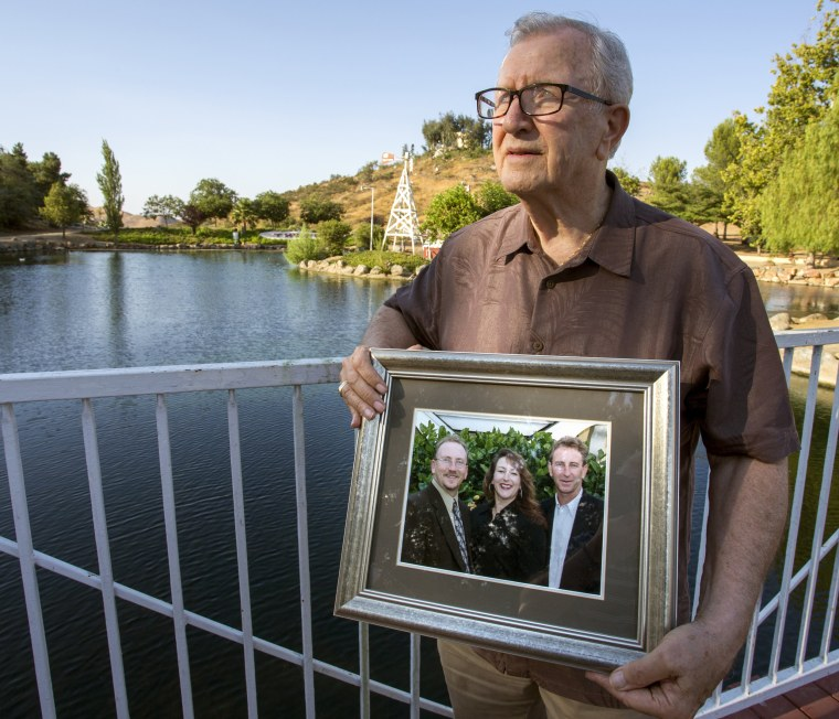 Image: Frank Kerrigan holds onto a photograph of his three children