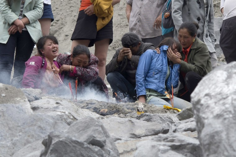 Image:  Mourners wait at the site of the landslide while rescue workers clear rubble in search of bodies on June 25.