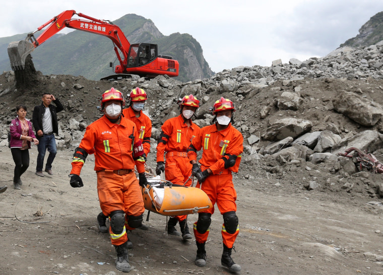 Image: Rescue workers carry a victim out of the rubble on June 25.