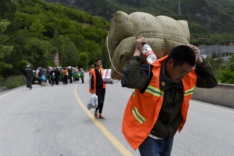 Image: A man carries relief supplies as he heads to a landslide area on June 25.