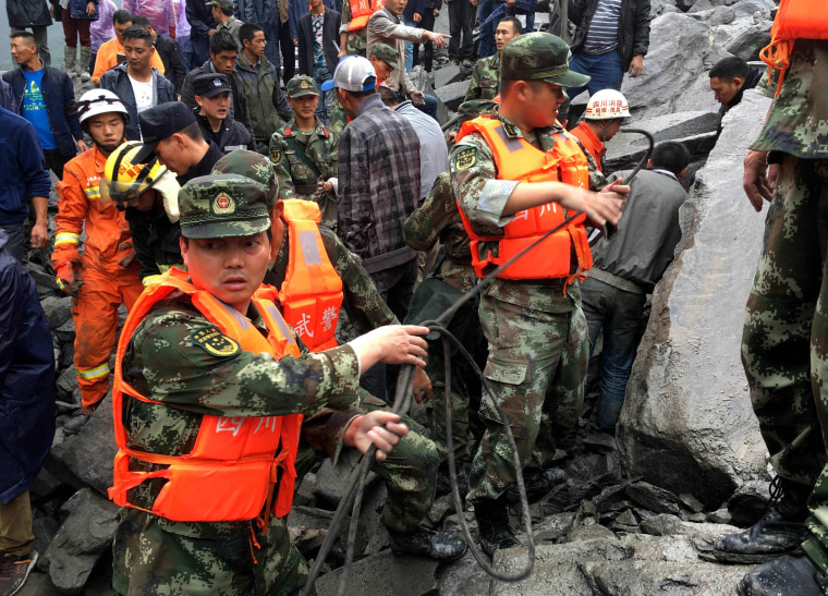 Image: Chinese military police and rescue workers look for victims on June 25.