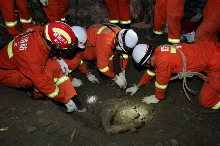 Image: Rescue workers try to remove the body of a victim at the site of the landslide on June 24.