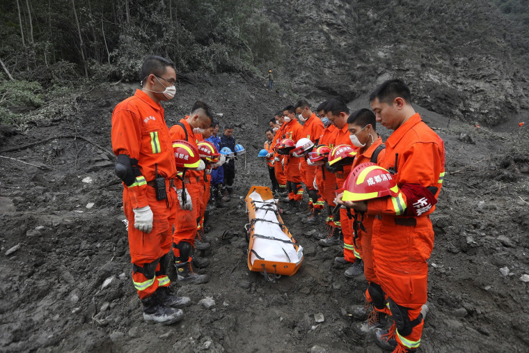 Image: Rescue workers stand in silent tribute before evacuating a body on June 25.