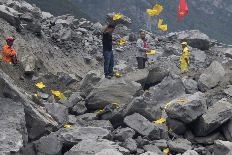 Image: Relatives toss paper offerings to appease the dead at the site of the landslide on June 25.