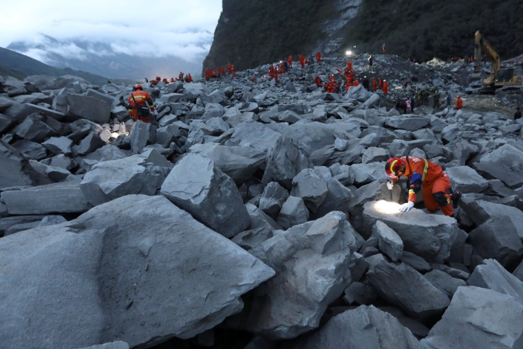Image: Rescue workers search for survivors into the night on June 24.