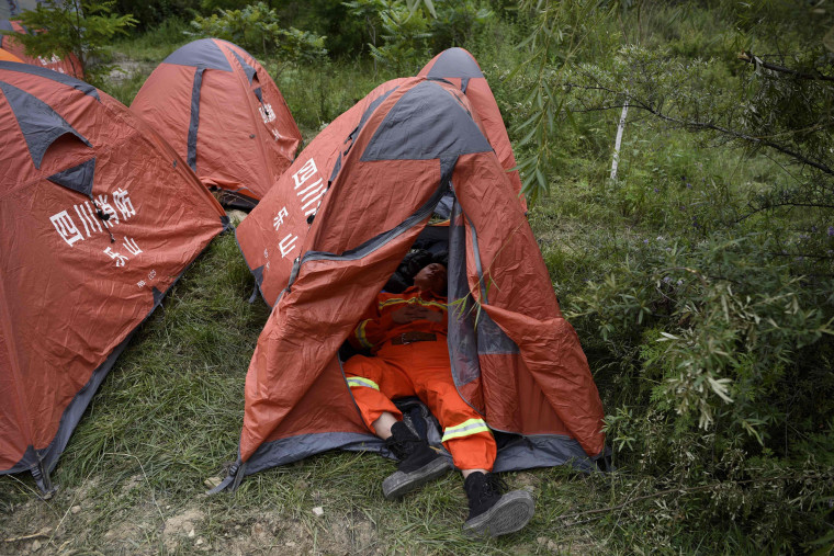 Image: A rescue worker takes a rest in a tent on June 24.