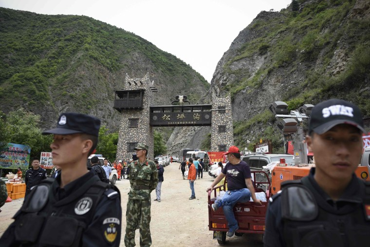 Image: Police stand their guard at an entrance to the road that leads to the village of Xinmo, in Maoxian county in China's Sichuan province, where a landslide buried the village and more than 100 of its residents on June 24, 2017.