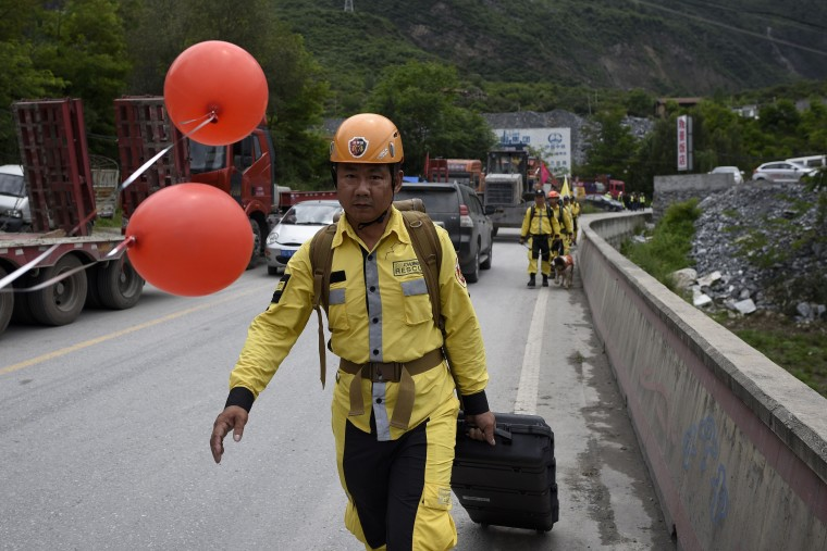 Image: Rescuers walk along the road into the landslide area, where the search for victims has continued on June 25.