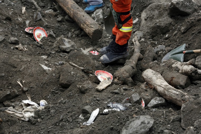 Image: Household goods are scattered among the debris as rescue workers search for victims on June 25.