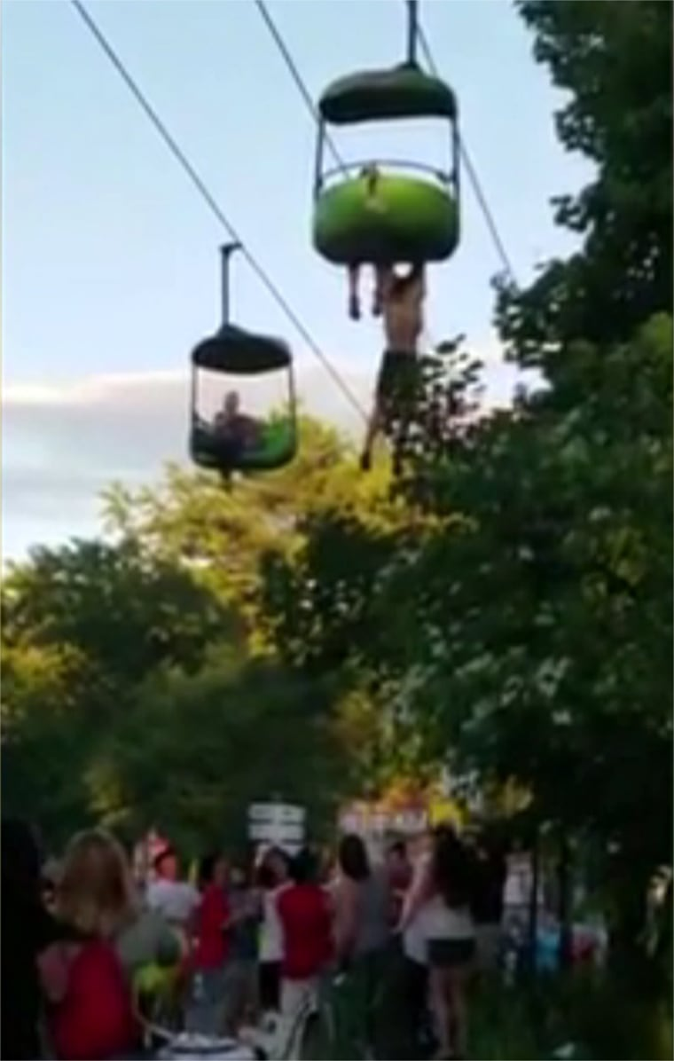 Image: A 14-year-old hangs from a amusement park ride before falling into the arms of good Samaritans