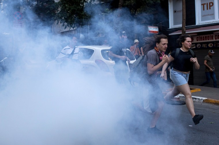 Image: LGBT supporters run from tear gas fired by police after attempting to march to Taksim Square