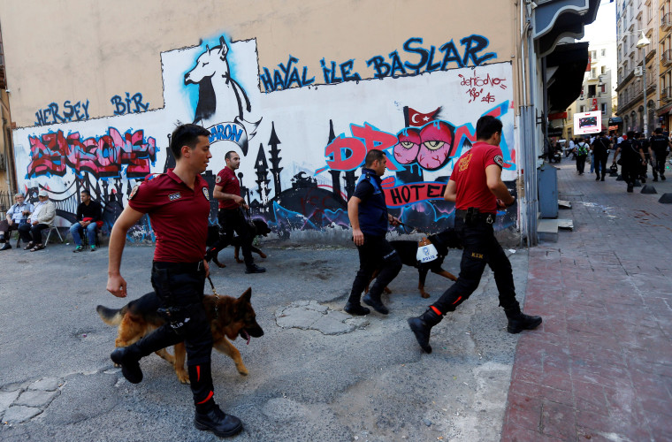 Image: Police officers with dogs chase LGBT rights activists as they try to gather for a pride parade in central Istanbul
