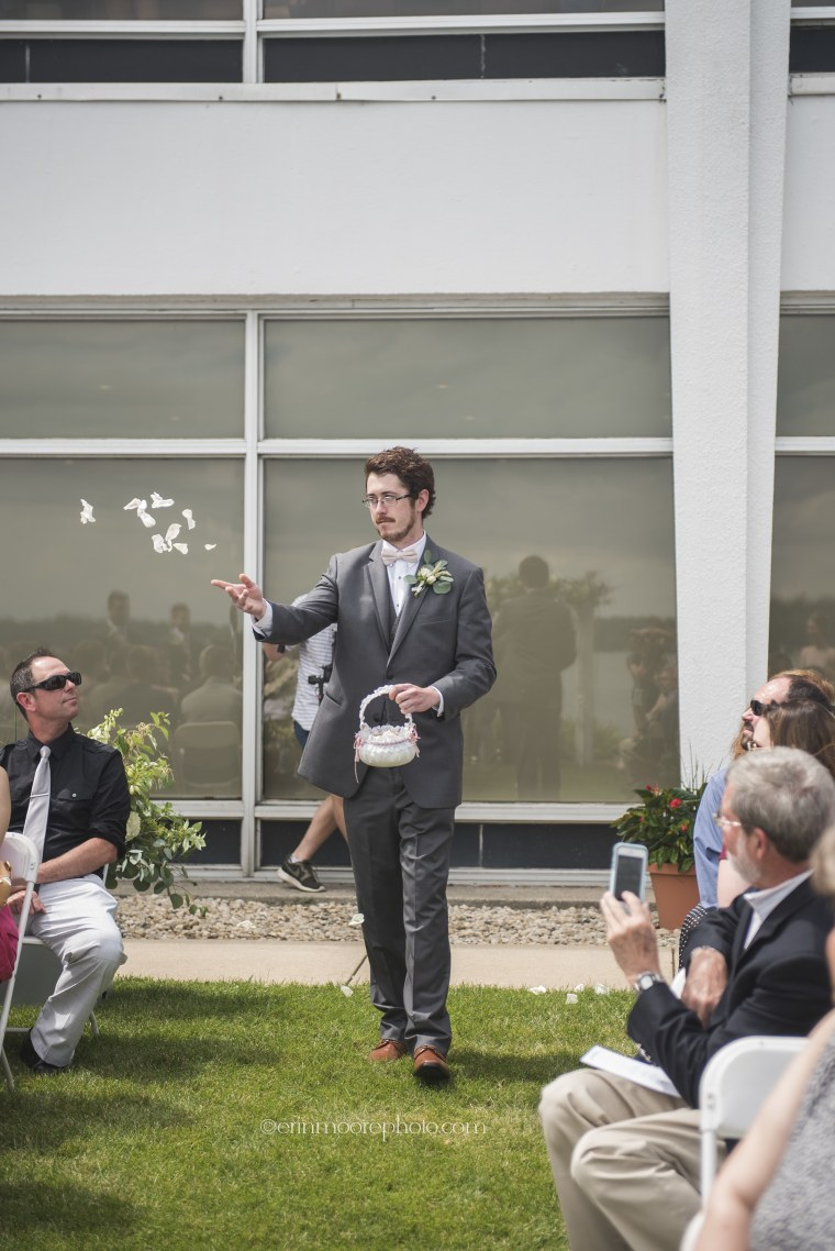 Man tosses rose petals as the flower man at his cousin's wedding