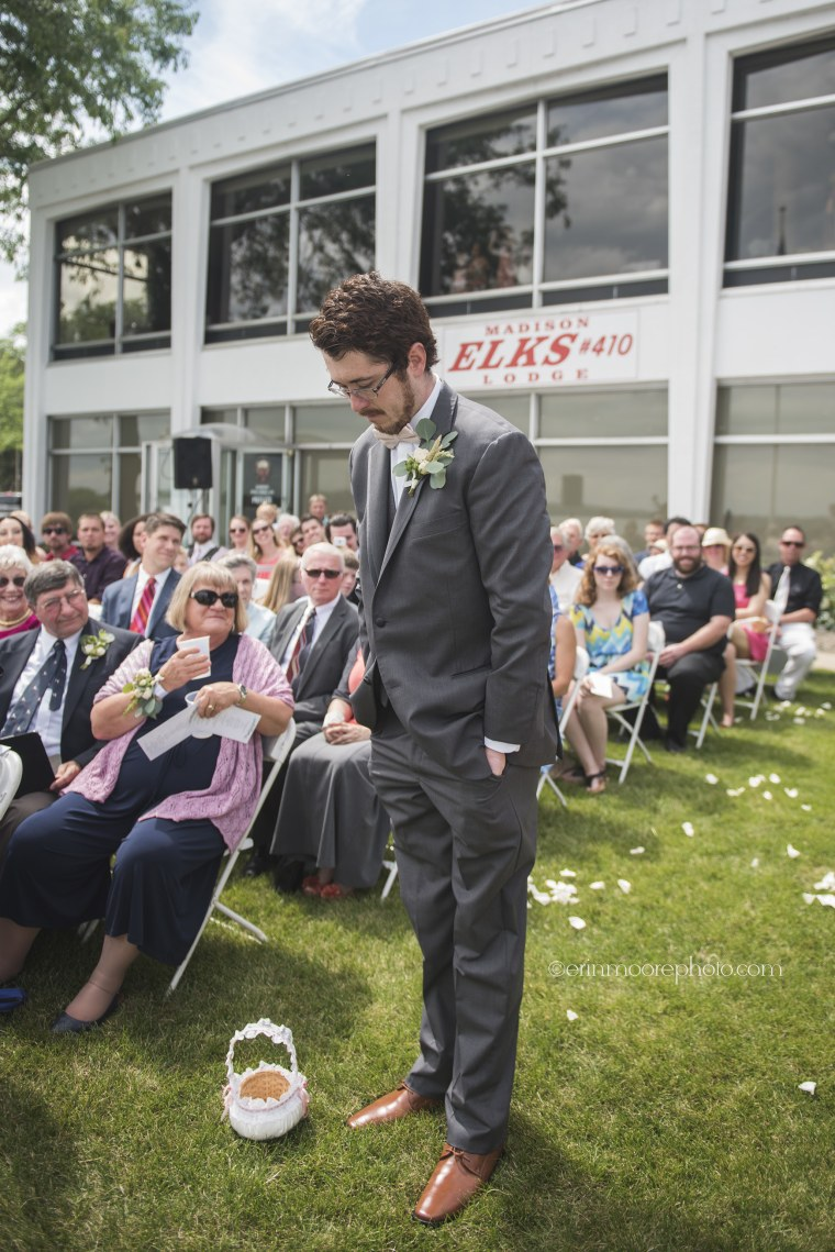 Twenty-eight year old man tosses rose petals at cousin's wedding as flower man