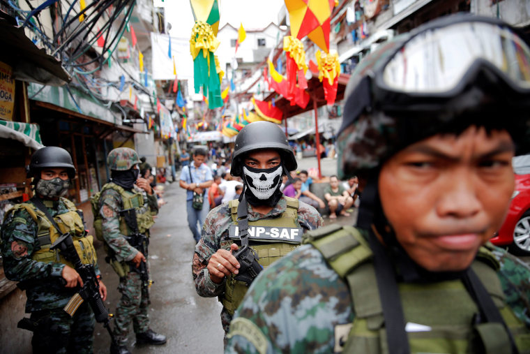 Image: Armed security forces take a part in a drug raid, in Manila