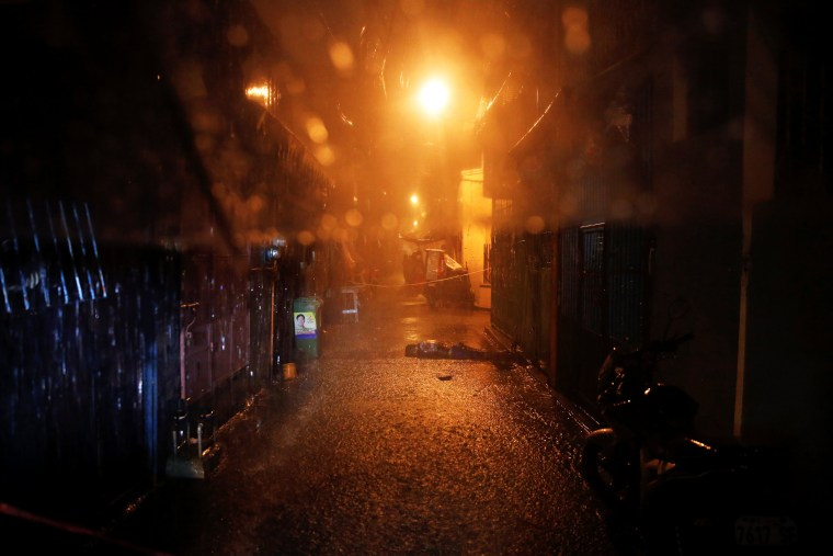 Image: Heavy rain pours as the body of a man killed by unidentified gunmen riding motorcycles is left in a narrow alley in Manila