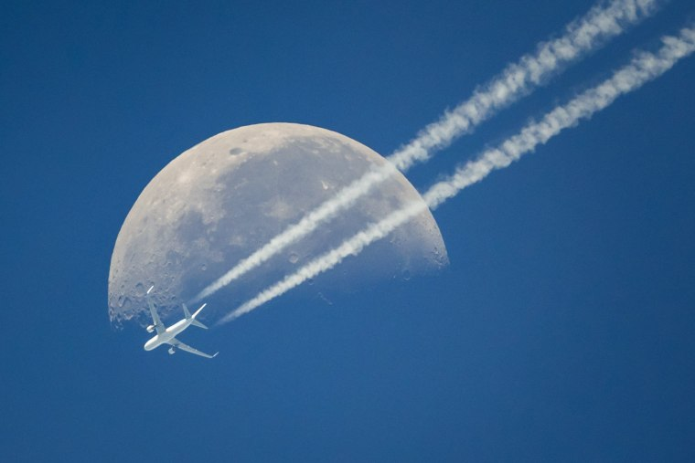 Image: A commercial airplane flies past the moon above Geneva
