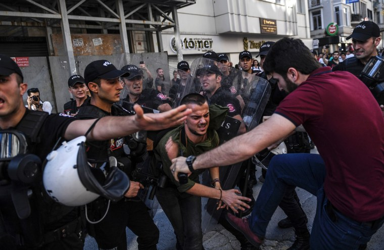 Image: A plain-clothes police officer kicks a member of a group of LGBT rights activist as Turkish police prevent them from going ahead with a Gay Pride annual parade
