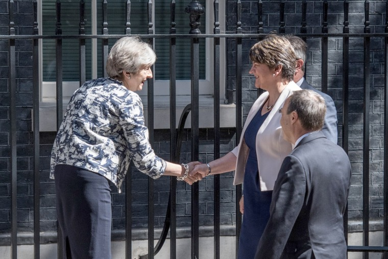 Image: Britain's Prime Minister, Theresa May (L), greets Arlene Foster, the leader of Northern Ireland's Democratic Unionist Party (C), deputy leader of the Democratic Unionist Party, Nigel Dodds (R) and DUP MP Jeffrey Donaldson (at rear).