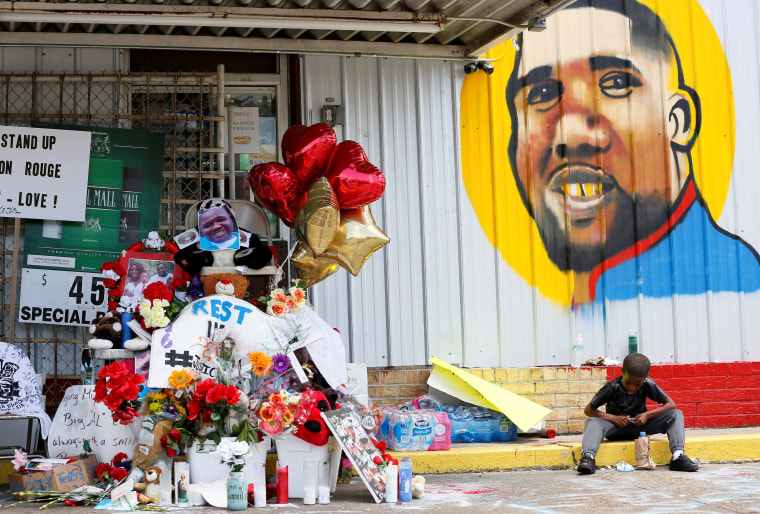 Image: FILE PHOTO: A boy sits next to a makeshift memorial outside the Triple S Food Mart where Alton Sterling was fatally shot by police in Baton Rouge