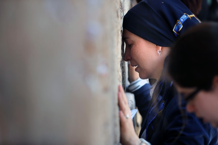 Image: Jewish women pray at the men's section of the Western Wall in Jerusalem.