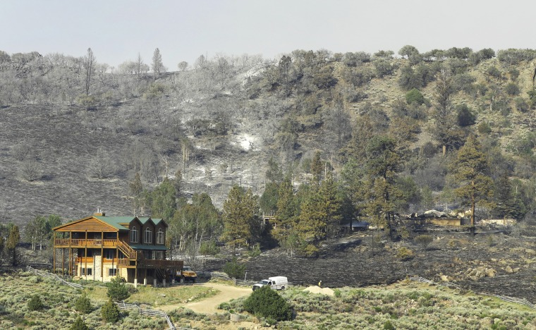 """Image: A home that was saved, left, stands next to one that burned to the ground during the """"Brian Head Fire"""" wildfire above Panguitch Lake"""