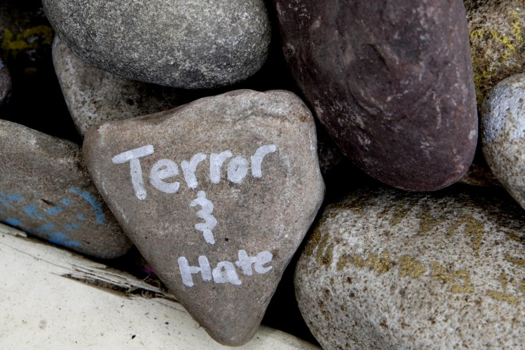 """Image: A rock has the words """"terror and hate"""" written on it at an art installation"""