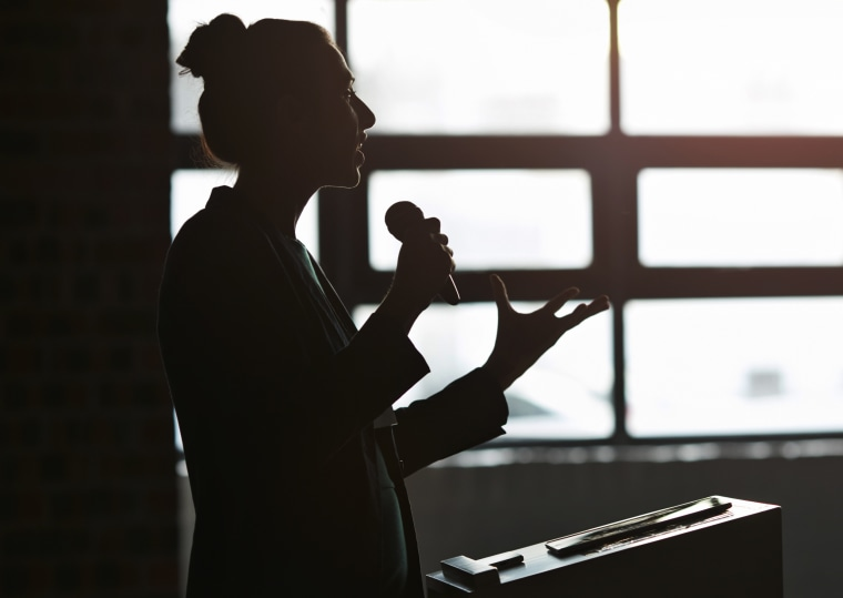 Image: A woman speaks using a microphone