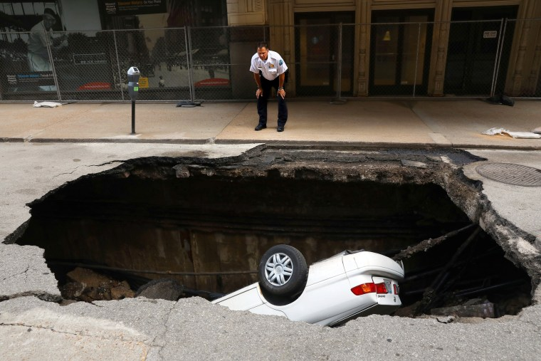 Image: St. Louis police officer looks over a large hole in 6th Street