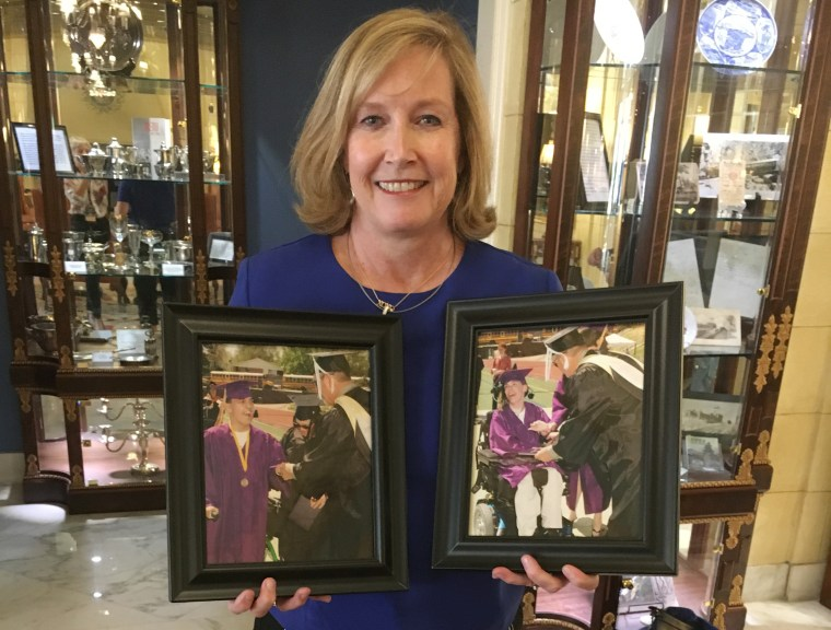Image: Kelly Stahlman holds framed photographs of her twin sons Mark and Eric receiving their high school certificate