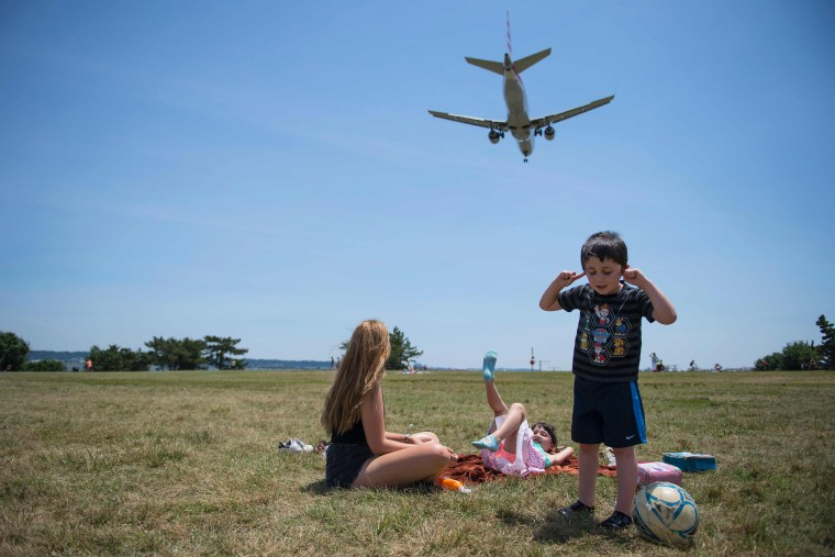 Image: A young boy plugs his ears as planes land at Reagan National Airport