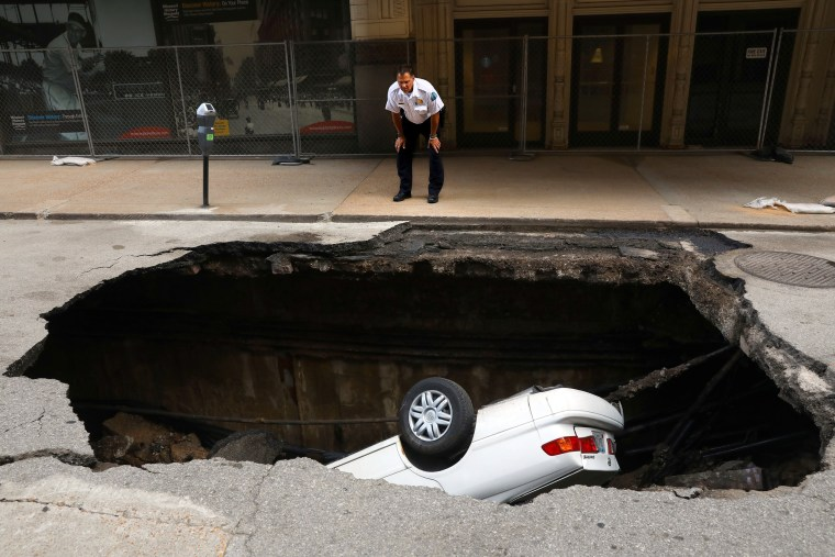 Image: St. Louis police officer looks over a large sinkhole