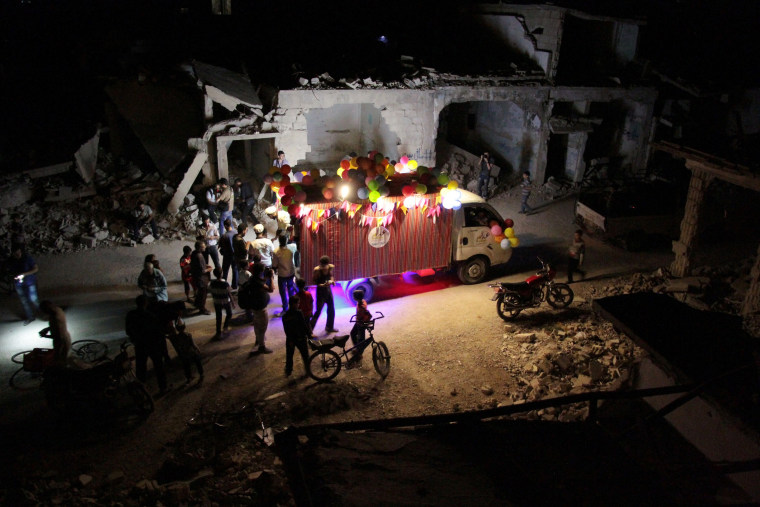 Image: Syrians gather around an ice-cream truck amid destroyed buildings in Douma