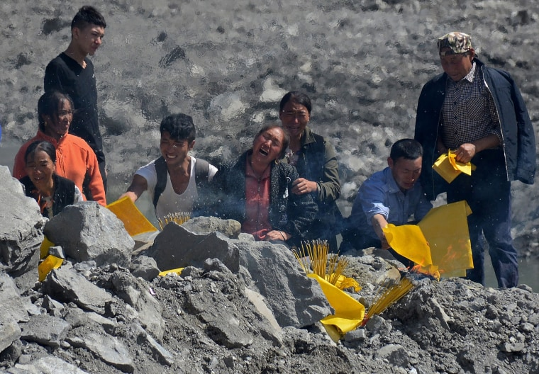 Image: Relatives mourn at the site of a landslide in Xinmo village in China's Sichuan province