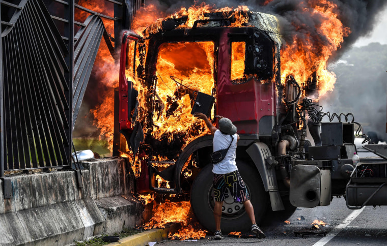 Image: A truck burns after being set on fire during a demonstration by opposition activists