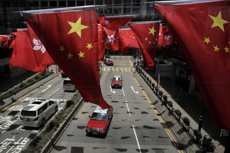 Image: China and Kong Hong national flags are displayed outside a shopping center