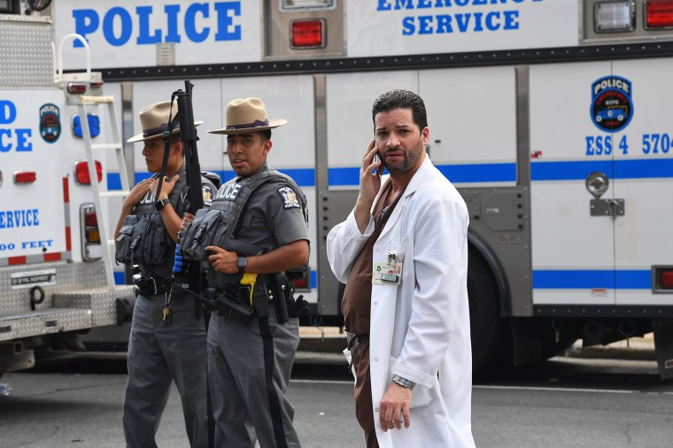 Image: A hospital staff member talks on his phone as he walks past police outside the Bronx-Lebanon Hospital