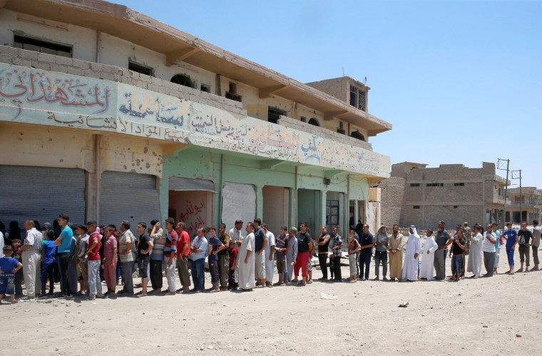Image: Displaced Iraqi residents queue as they wait for the food distribution by an aid organization during the first day of Eid-al Fitr celebration in West Mosul, June 25.