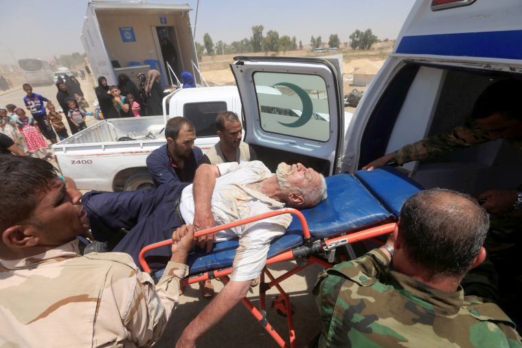 Image: Iraqi soldiers carry a displaced man, who collapsed in exhaustion after fleeing from Mosul on June 29.