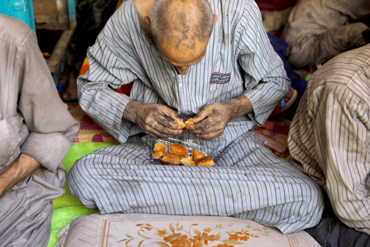 Image: A displaced Iraqi man who was among the rescued at the site of a battle eats bread on June 29.