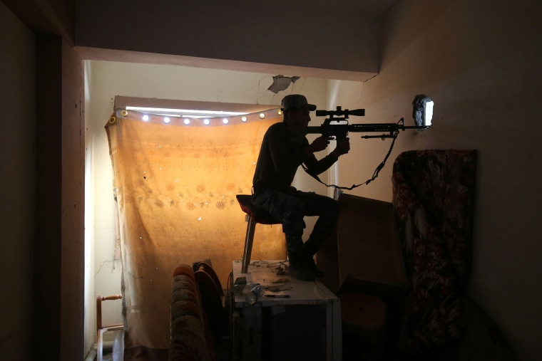 Image: An Iraqi forces member aims his gun towards an Islamic State position on June 24.