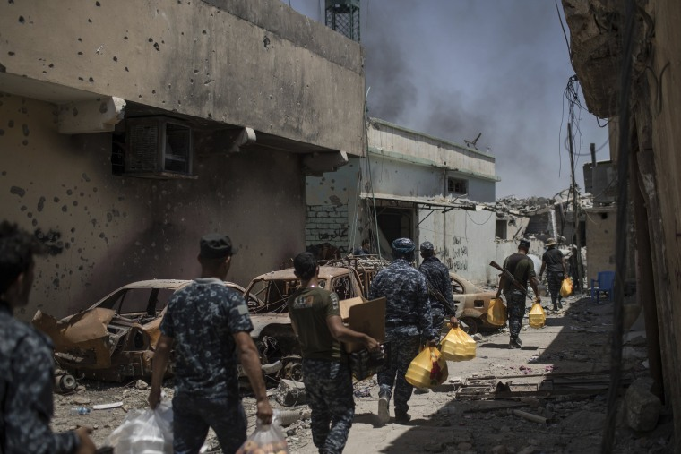 Image: Federal policemen carry food to the front line during fighting against Islamic State militants on June 26.