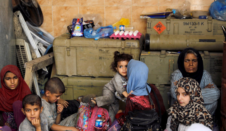 Image: Displaced Iraqi civilians who were rescued from the site of a battle rest among Iraqi forces on June 29.