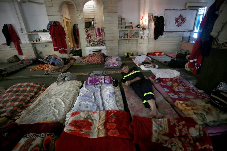 Image: Iraq civil defense search and rescue workers rest on June 27.