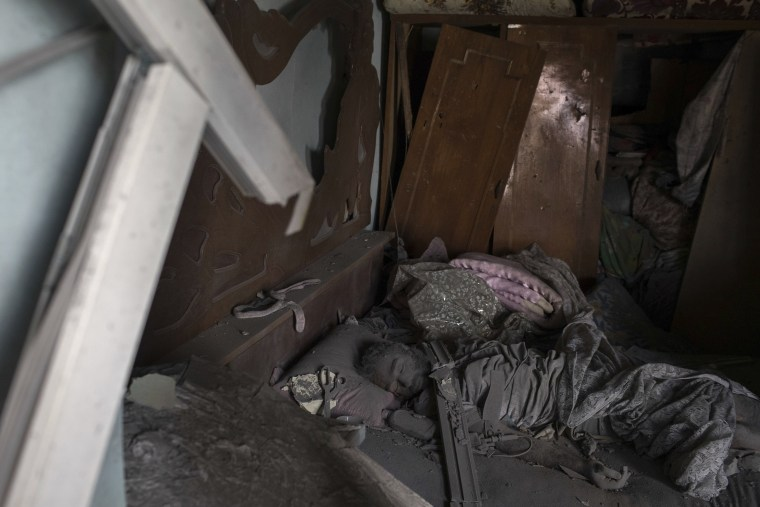 Image: The body of an alleged Islamic State militant lays on a bed in a destroyed house on June 30.