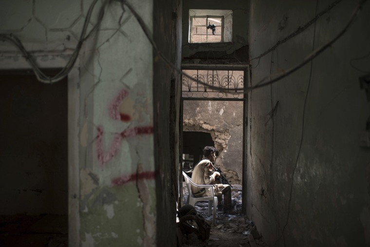 Image: An Iraqi Special Forces soldier guards an alley during fighting on June 30.
